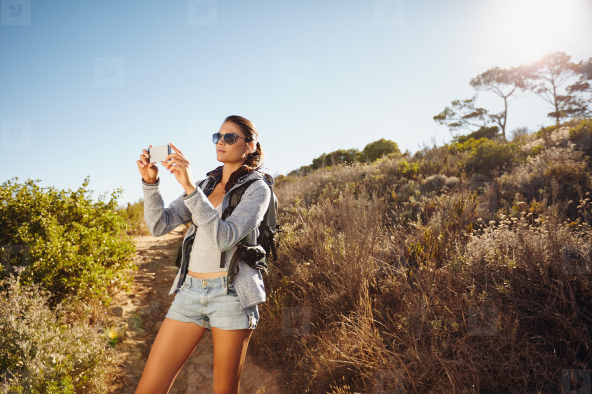 Hiking woman taking photo with smart phone