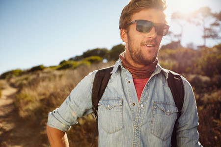 Happy young man hiking in countryside