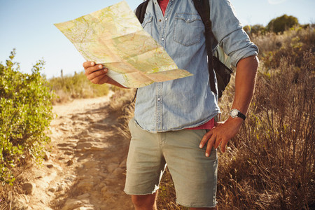 Man hiking in countryside with a map