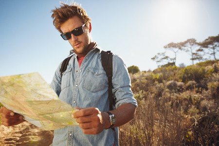 Handsome hiker using a map