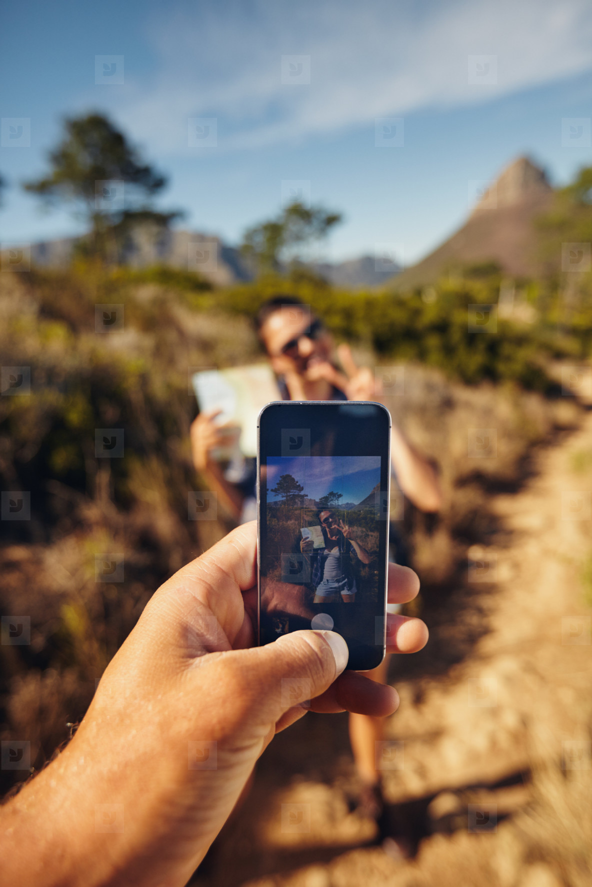Hiker couple taking pictures with smartphone