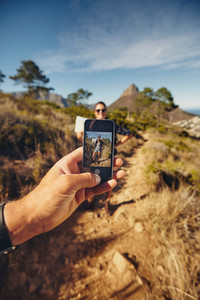 Man talking pictures of a woman with mobile phone   Hiking trip