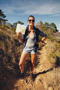 Beautiful woman hiker posing with a map