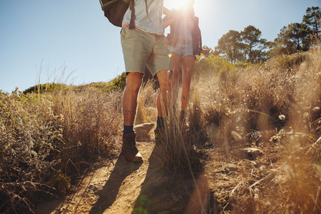 Man and woman hikers walking on dirt trail