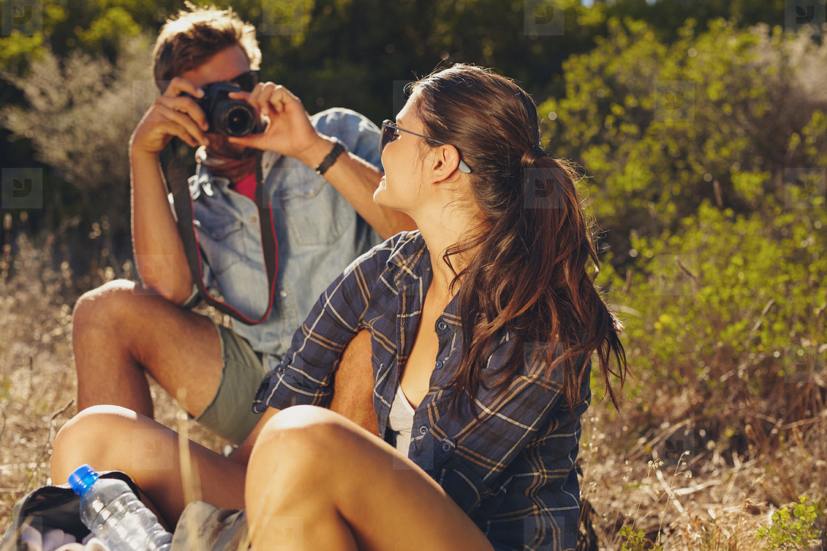 Young couple taking pictures on hiking trip