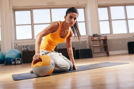 Fit young woman exercising with kettle bell