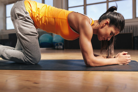 Strong woman exercising on fitness mat