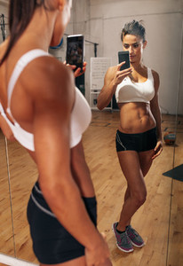 Muscular young woman taking a selfie in gym mirror