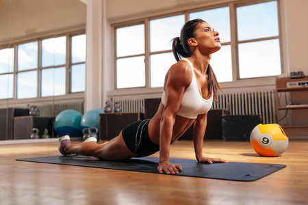 Woman doing core stretch in gym