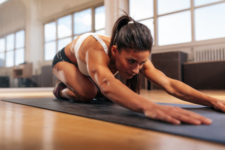 Muscular woman doing stretching workout in gym