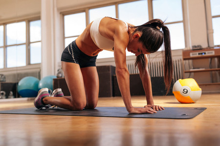 Muscular woman exercising on fitness mat