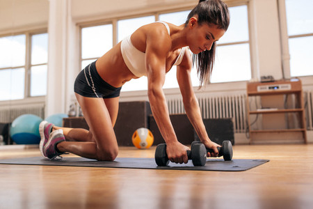 Powerful woman doing push ups on dumbbells