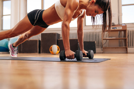 Fitness woman doing push ups exercise with dumbbells