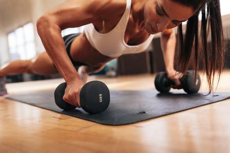Muscular woman doing push ups on dumbbells