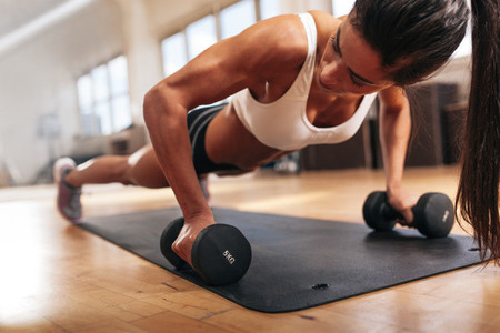 Gym woman doing pushups on dumbbells