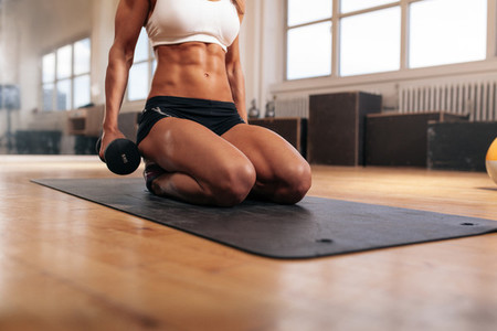 Muscular woman exercising with dumbbells