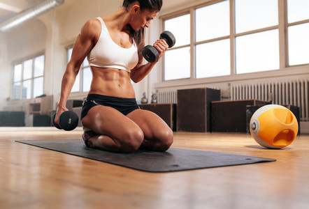 Fit woman working out at the gym with dumbbells