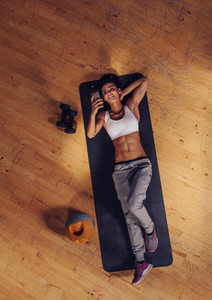 Smiling fitness female using mobile in gym