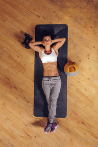 Fitness woman relaxing on yoga mat