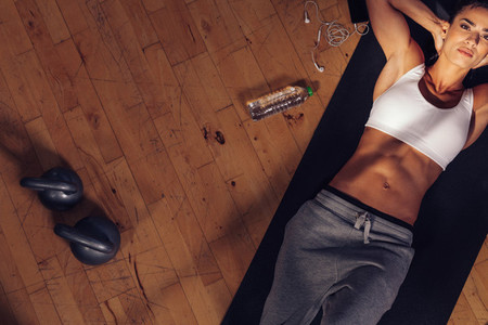 Fitness model lying on exercise mat