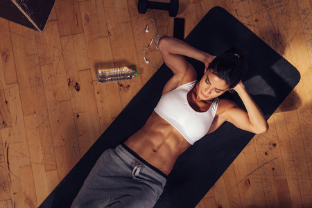 Sporty young woman doing sits up at gym