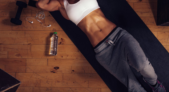 Woman with muscular abs lying on yoga mat at gym