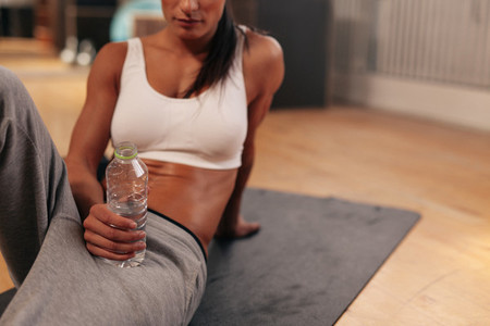 Relaxed woman at gym holding water bottle