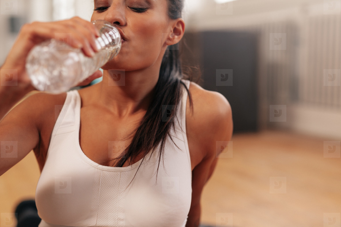 Fitness woman drinking water in a break