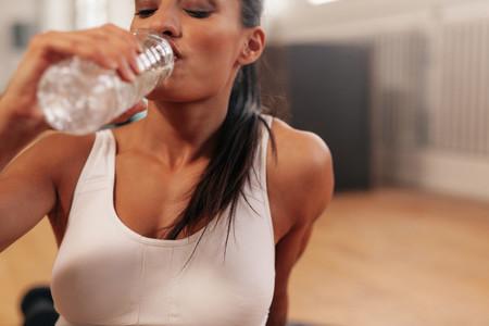 Fitness woman drinking water in a break