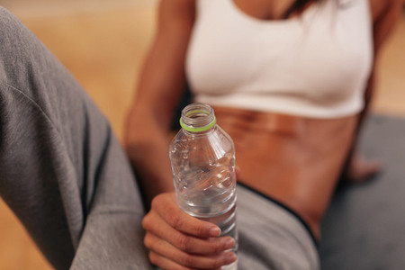 Water bottle in hand of a fitness woman
