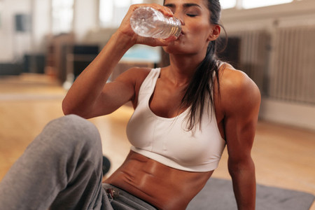 Fitness woman drinking water from bottle at gym