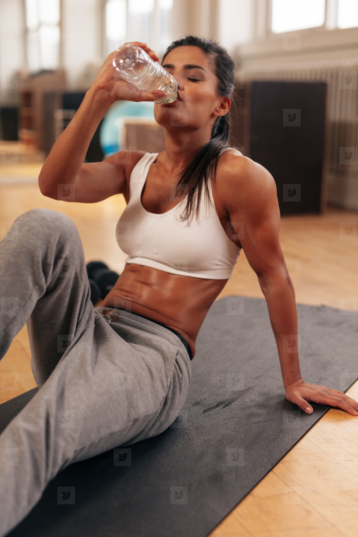 Fit young woman drinking water in the gym
