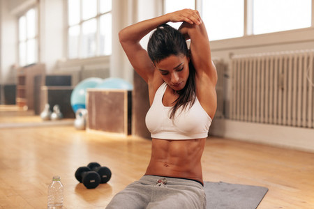 Fitness woman doing stretching exercise at gym