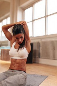 Muscular young woman stretching arms