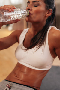 Fit young woman drinking water in a break