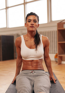 Determined young woman exercising at gym