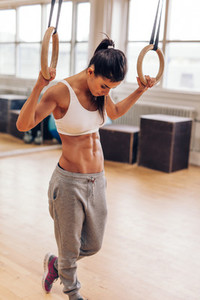 Fitness woman exercising with gymnastic rings