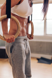 Muscular woman at gym doing dipping exercise