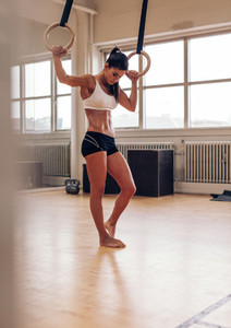 Woman resting after workout on gymnastic rings