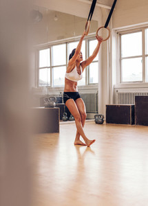 Sporty woman exercising with gymnastic rings