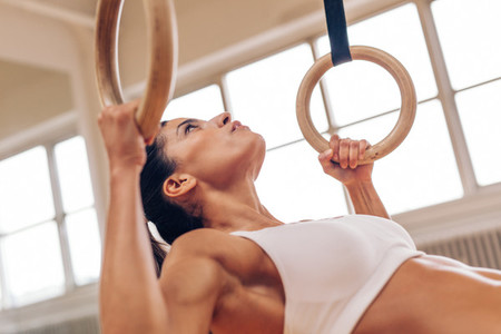 Strong woman doing pull ups with gymnastic rings