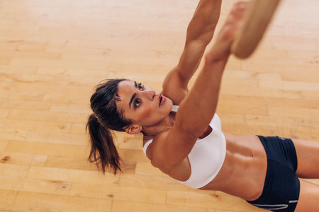 Determined young woman exercising with gymnastic rings