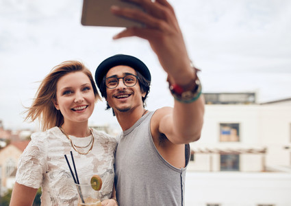 Two young friends taking self portrait at party