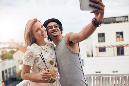 Friends taking a selfie at their outdoor rooftop party