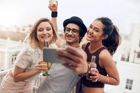 Multiracial people enjoying in party taking selfie