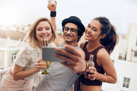 Multiracial people enjoying in party taking selfie