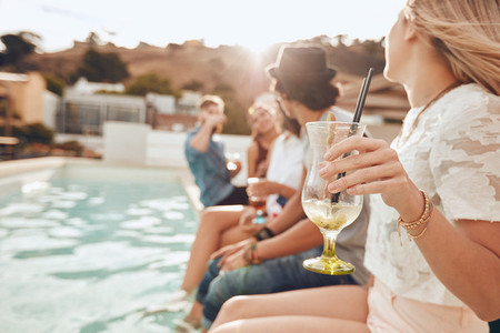 Young people enjoying a poolside party with drinks