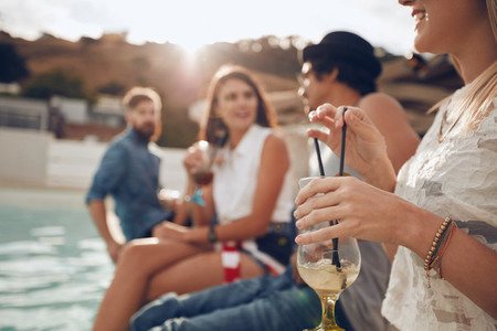 Young people enjoying a cocktail poolside party
