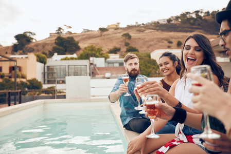Friends having wine at party by the poolside