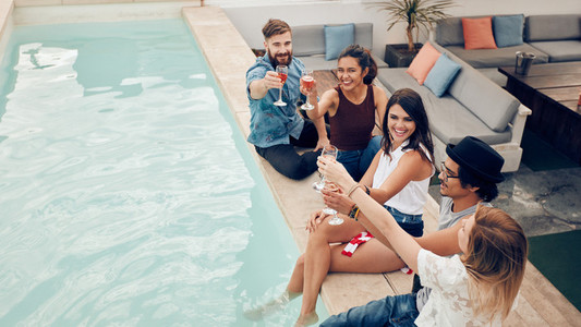 Group of friends toasting at pool party outdoor